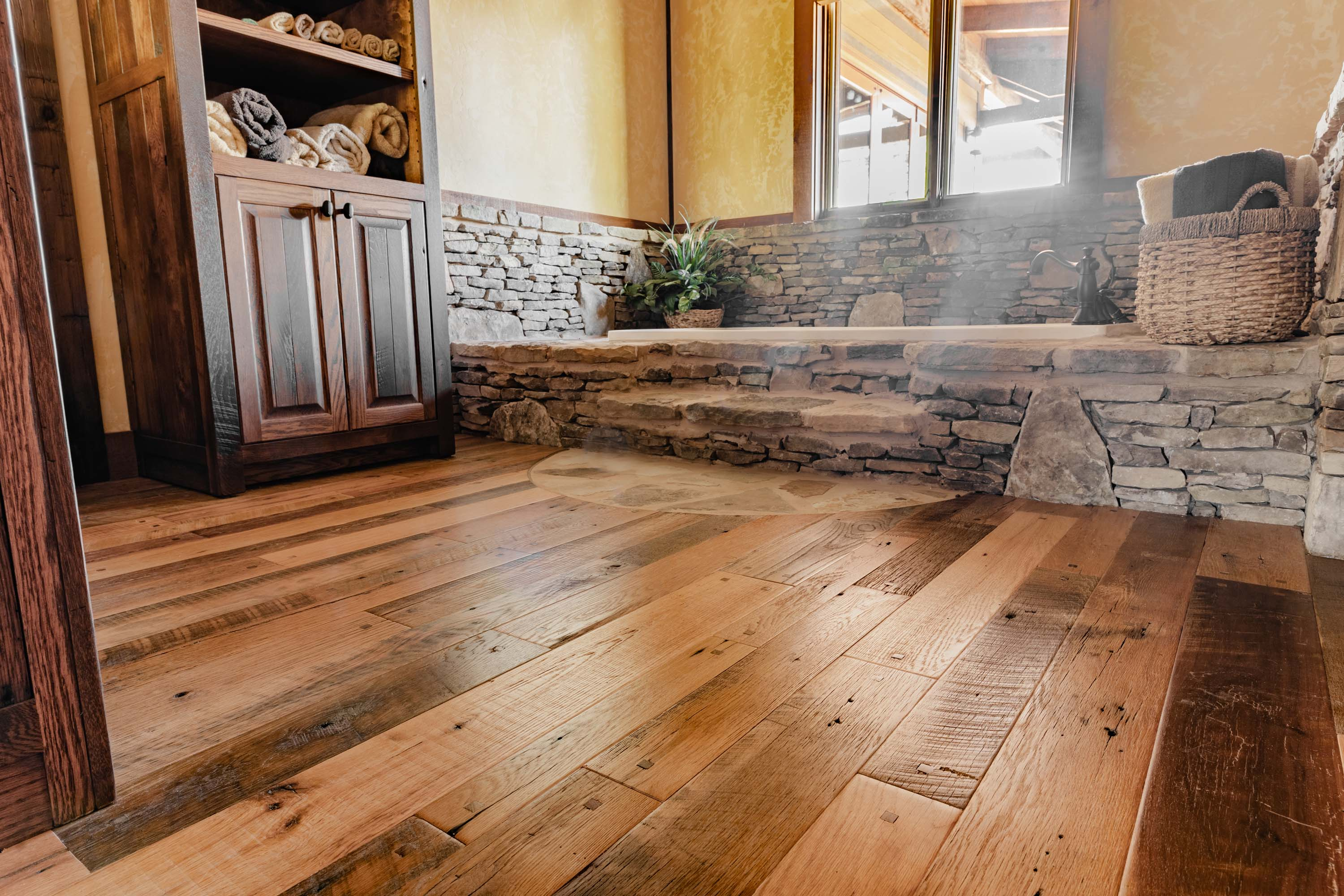 a bathroom in a cabin style house with reclaimed americana reclaimed wood flooring by Tennessee Wood Flooring. This hardwood floor is authentically made in the east tennessee area.