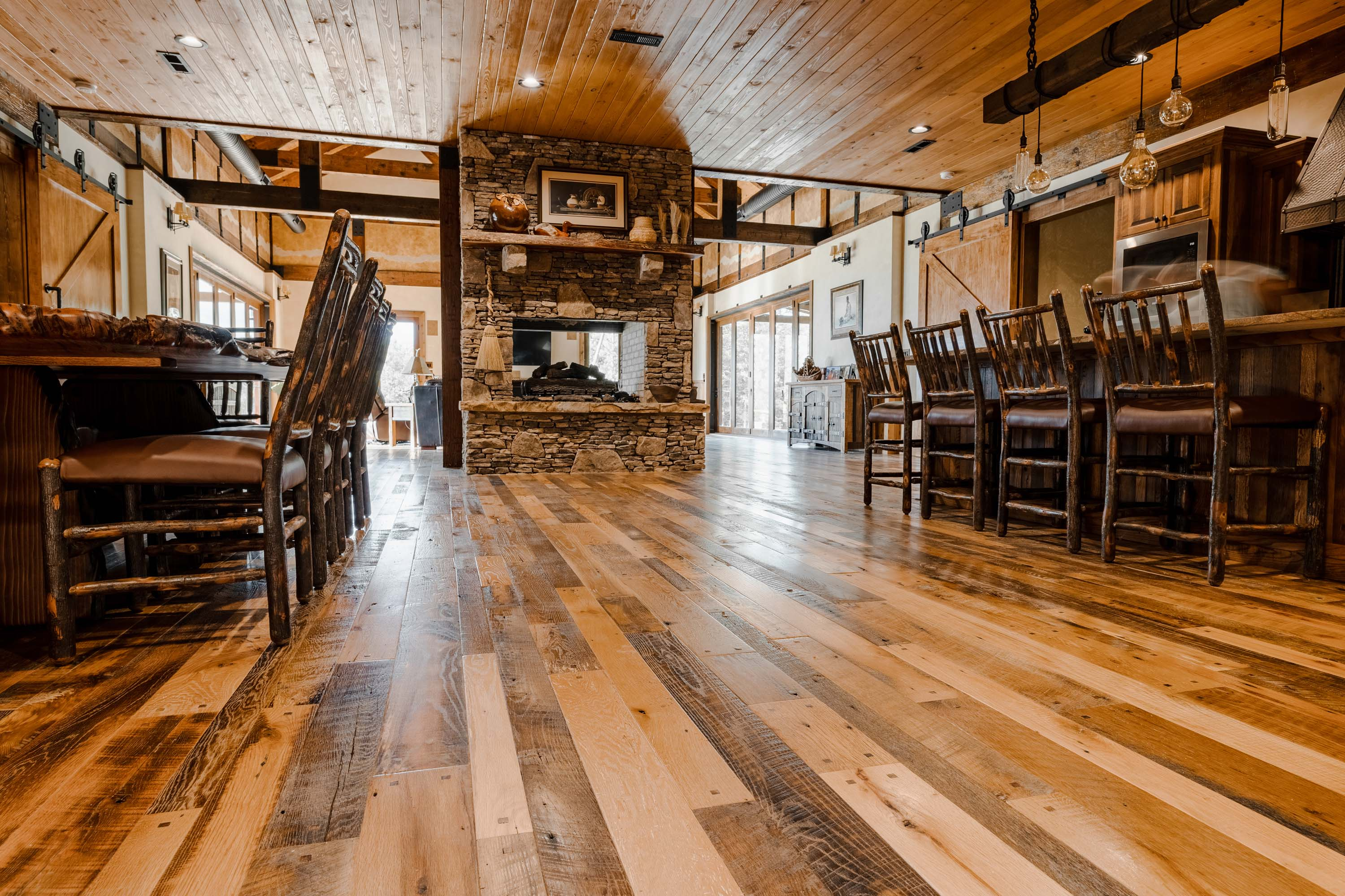 A dining room area in a cabin style house with reclaimed americana reclaimed wood flooring by Tennessee Wood Flooring. This hardwood floor is authentically made in the east tennessee area.