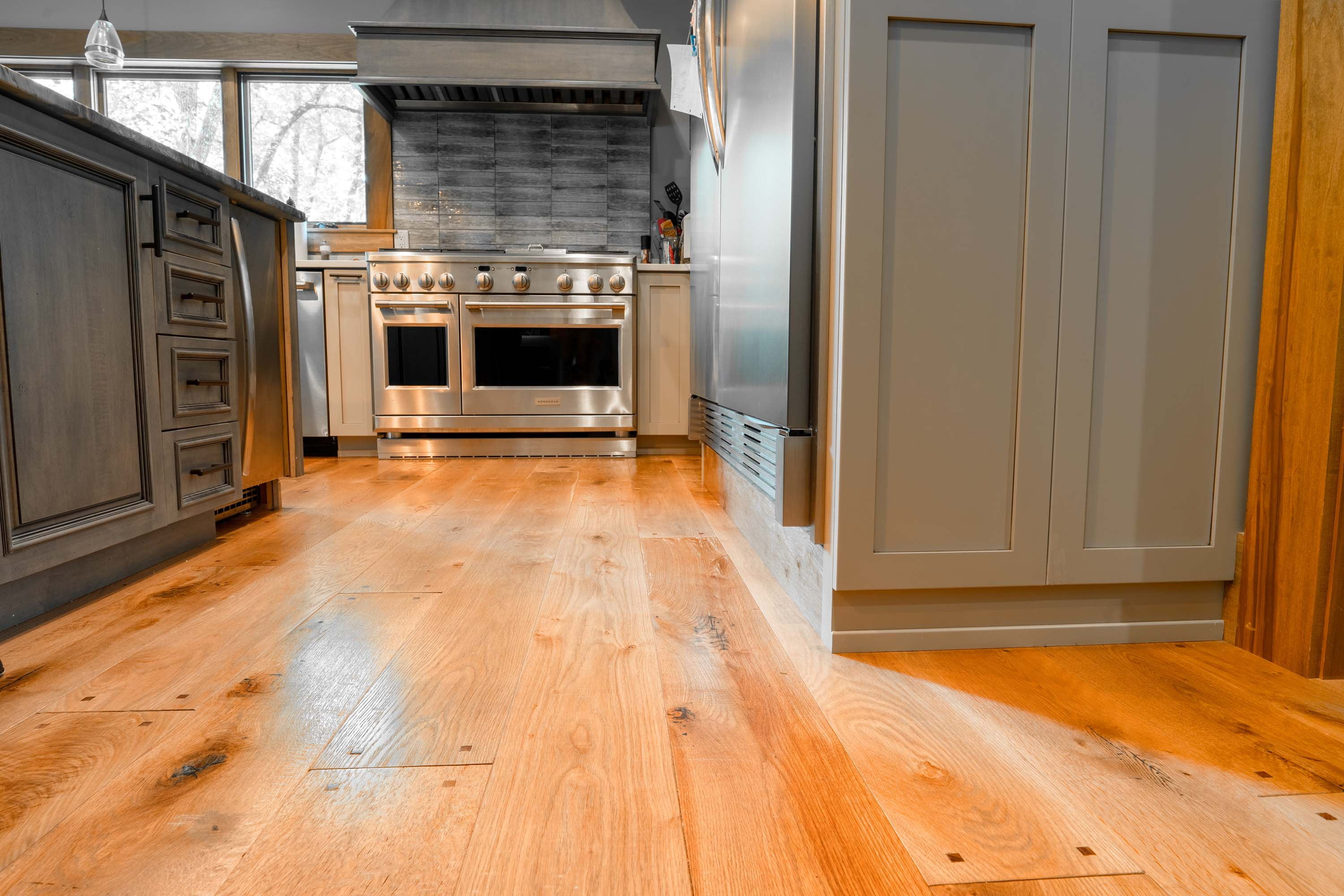 another angle of the kitchen with Montana Plank Reclaimed Wood Flooring by Tennessee Wood Flooring. Our Reclaimed Wood Floors are gathered and made in the hills of sevierville, tennessee.