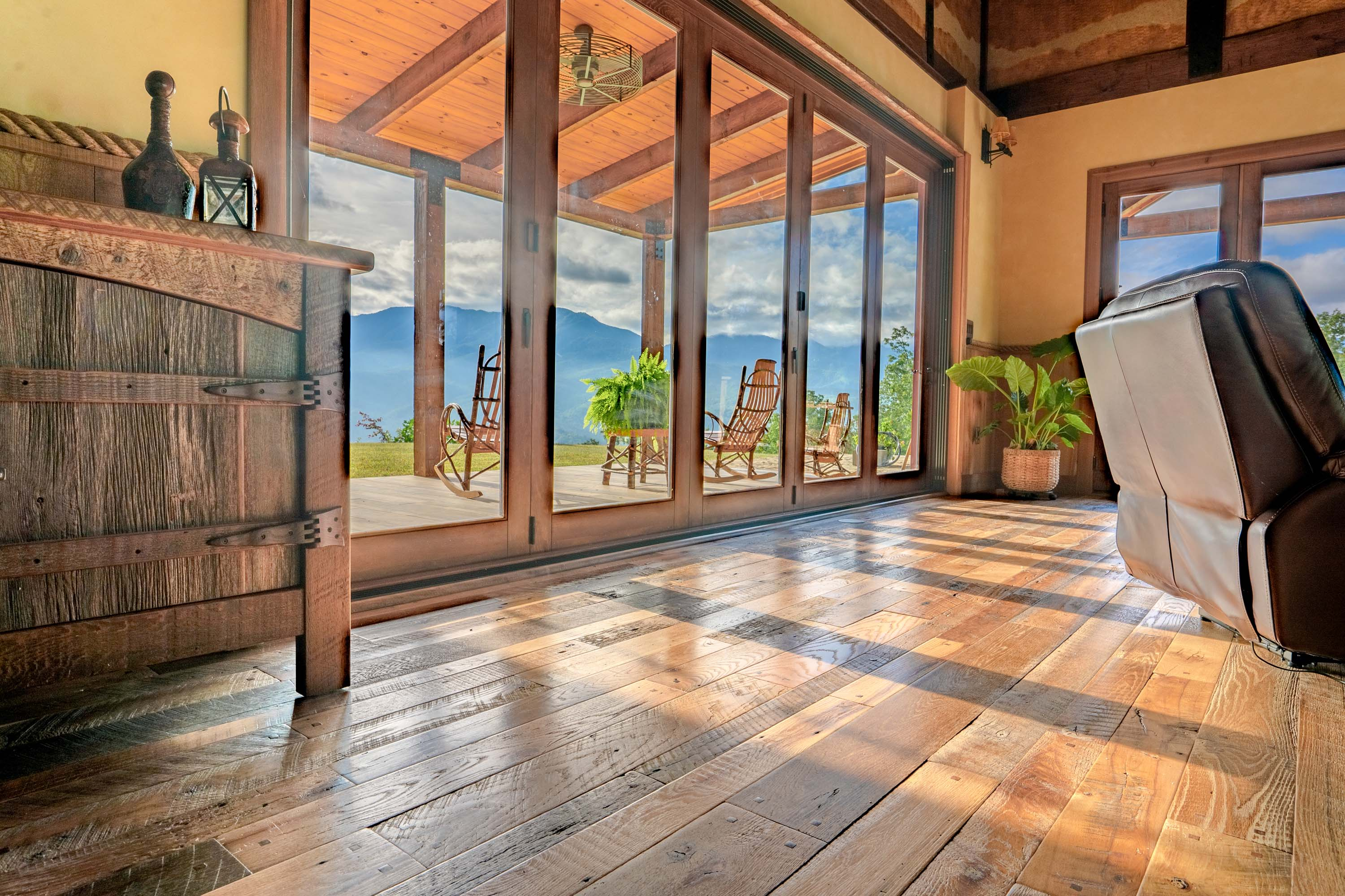 the glass doors near a living room in a cabin style house with reclaimed americana reclaimed wood flooring by Tennessee Wood Flooring. This hardwood floor is authentically made in the east tennessee area.