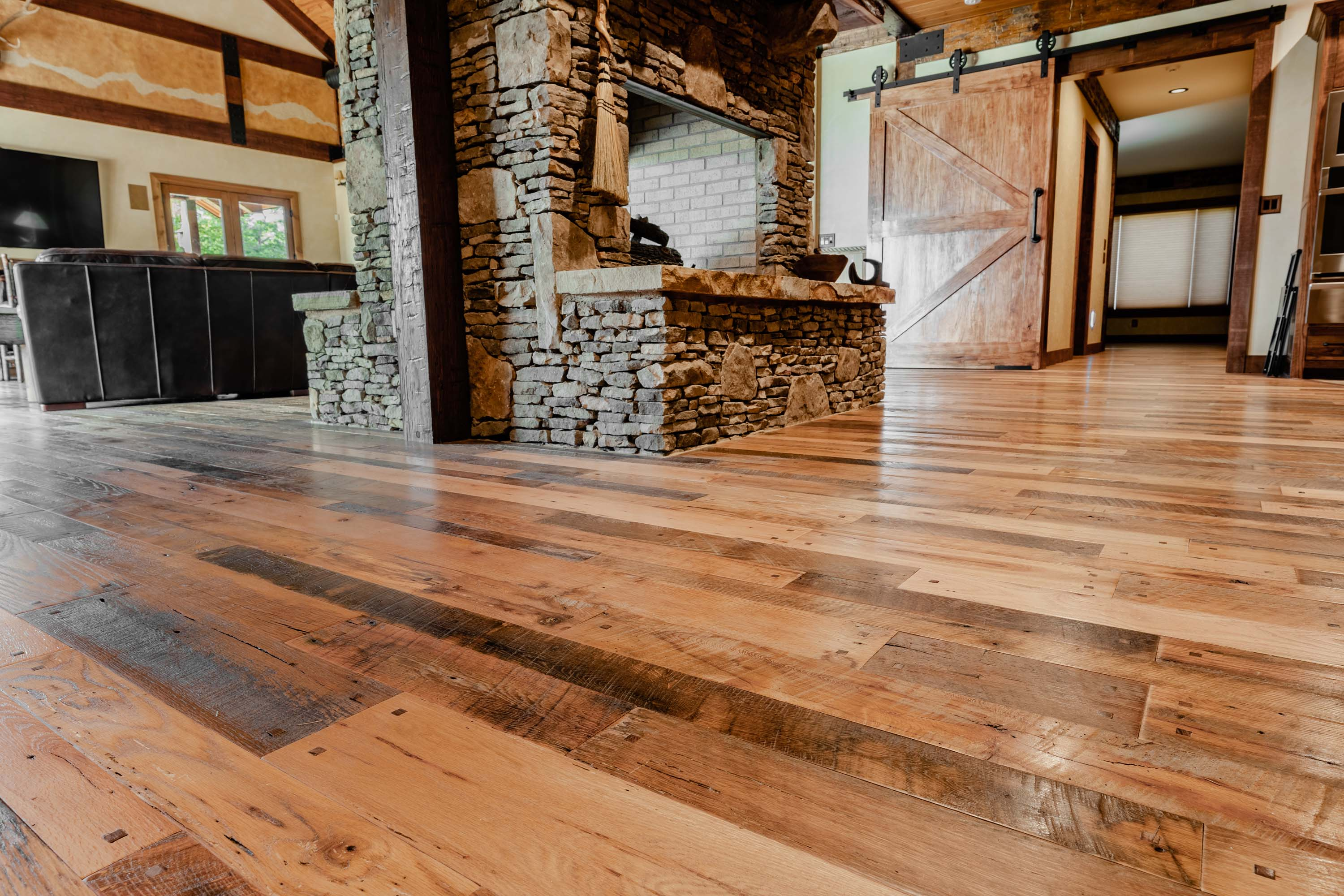 the fire place near the living room  in a cabin style house with reclaimed americana reclaimed wood flooring by Tennessee Wood Flooring. This hardwood floor is authentically made in the east tennessee area.
