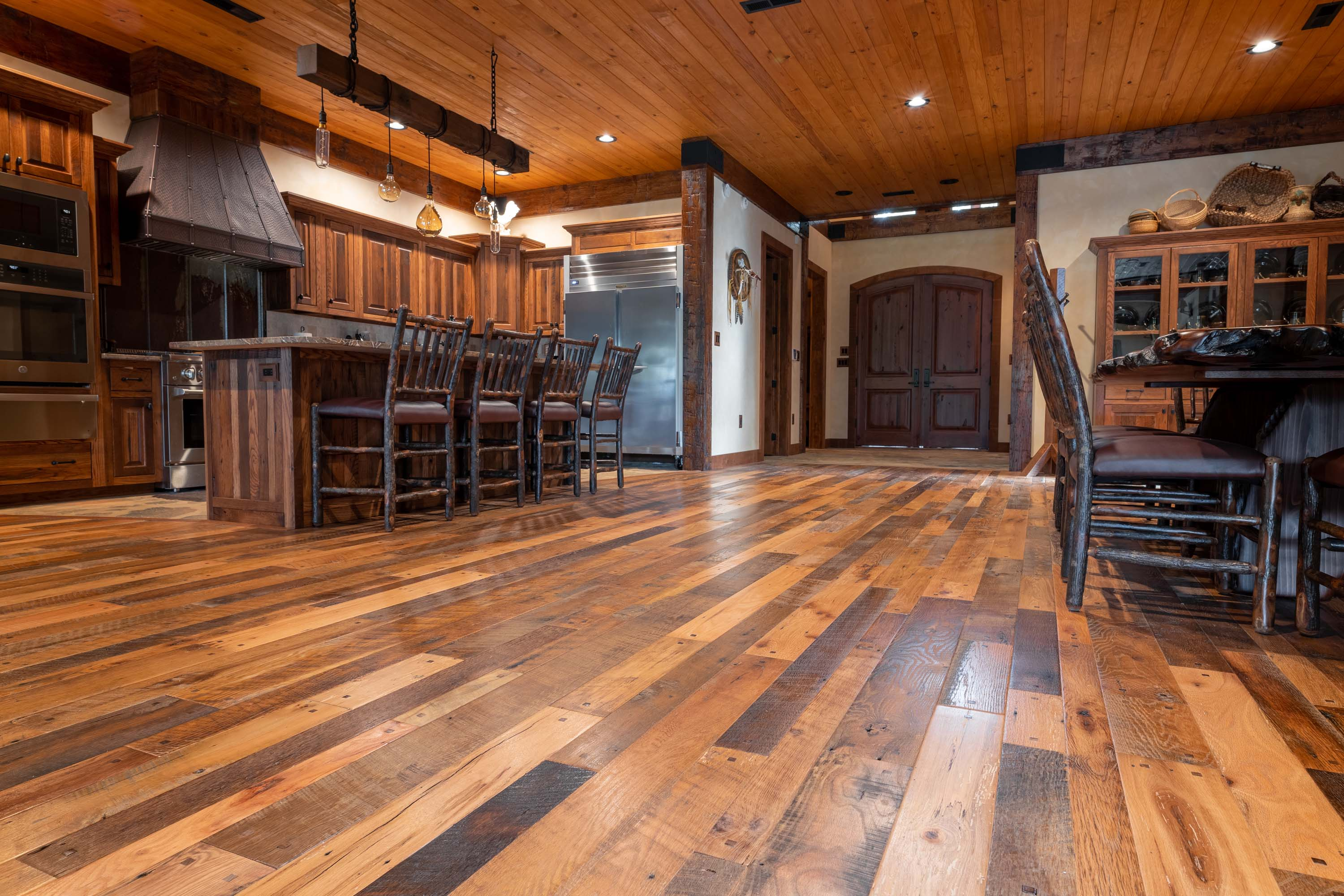 A kitchen in a cabin style house with reclaimed americana reclaimed wood flooring by Tennessee Wood Flooring. This hardwood floor is authentically made in the east tennessee area.