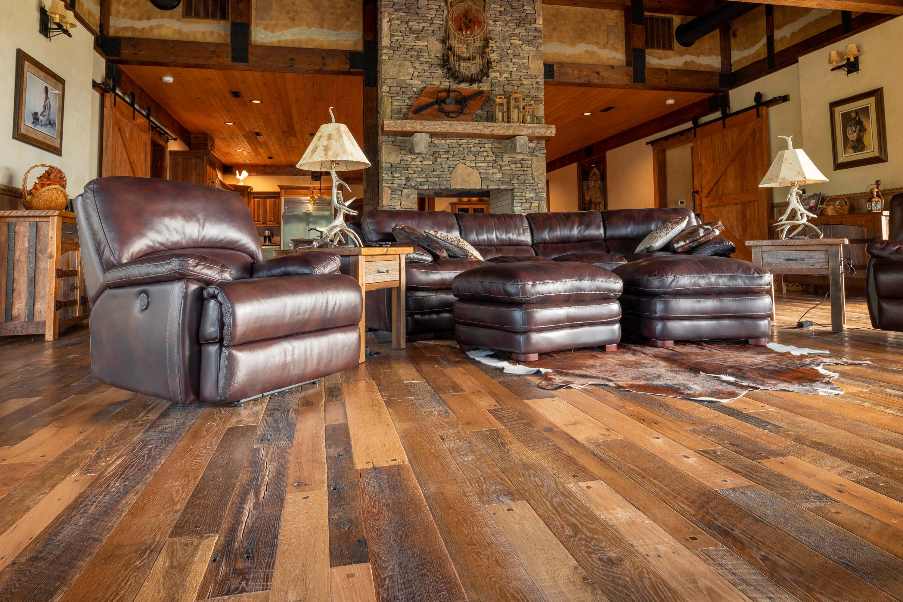 A living room in a cabin style house with reclaimed americana reclaimed wood flooring by Tennessee Wood Flooring. This hardwood floor is authentically made in the east tennessee area.