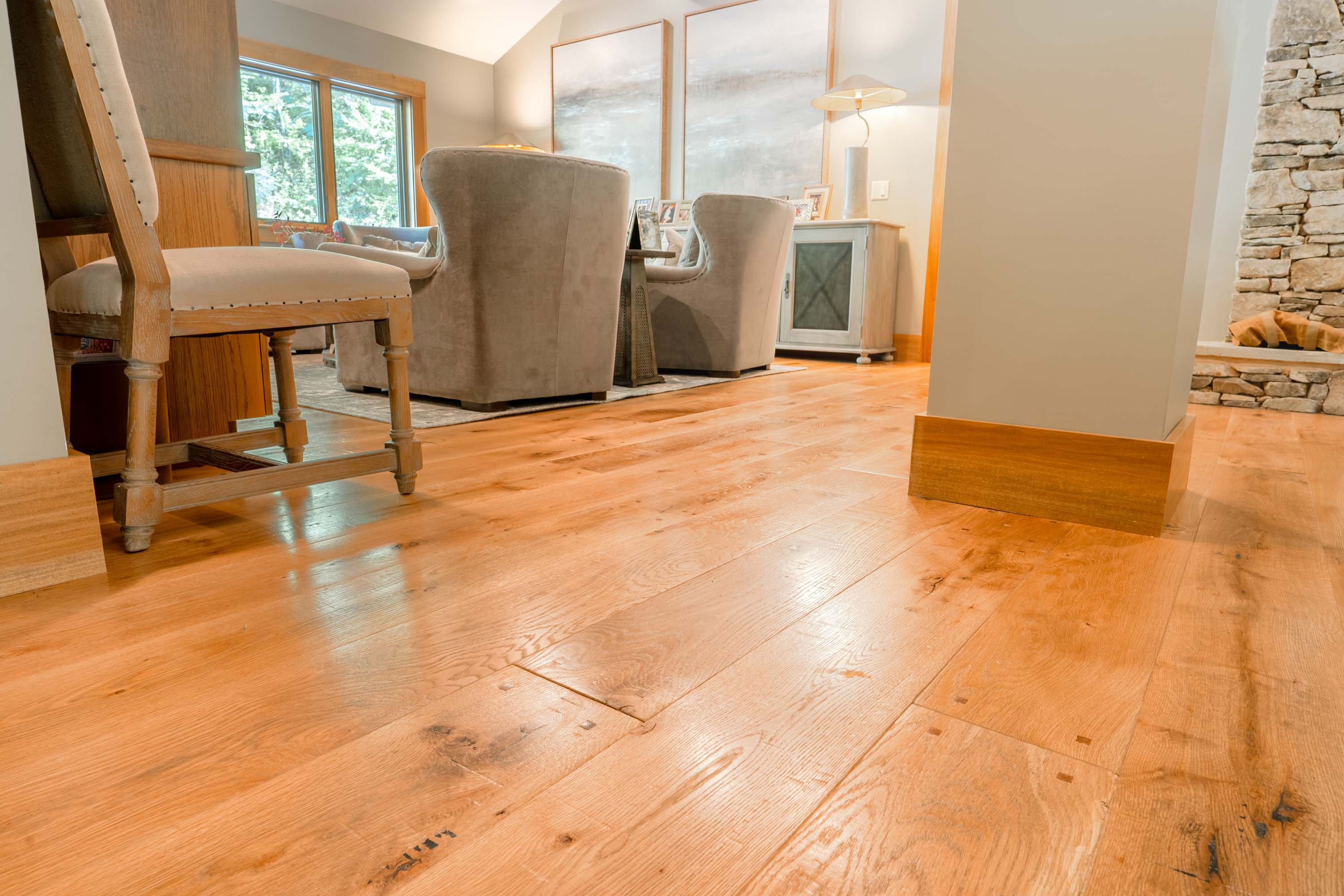 a living room with Montana Plank Reclaimed Wood Flooring by Tennessee Wood Flooring. Our Reclaimed Wood Floors are gathered and made in the hills of sevierville, tennessee.