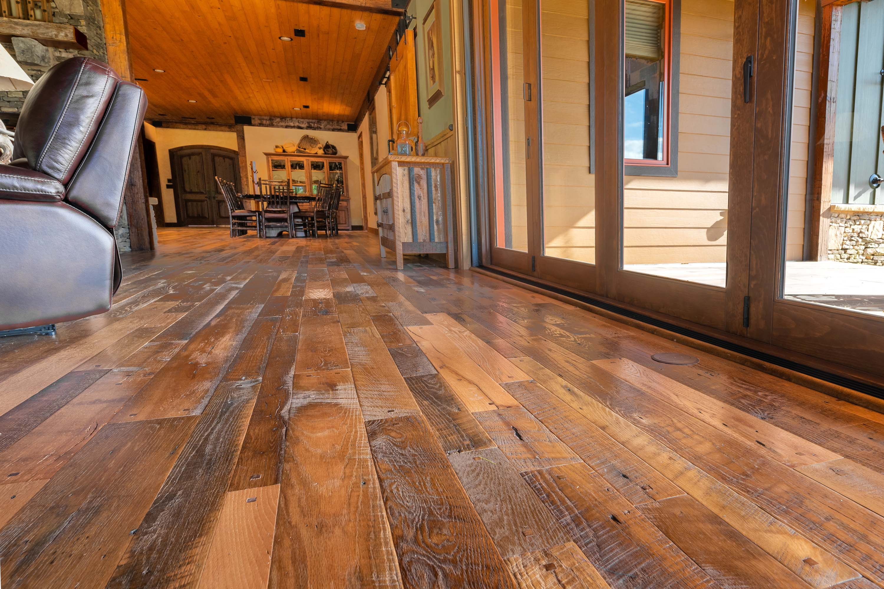 A living room with the glass doors near by in a cabin style house with reclaimed americana reclaimed wood flooring by Tennessee Wood Flooring. This hardwood floor is authentically made in the east tennessee area.
