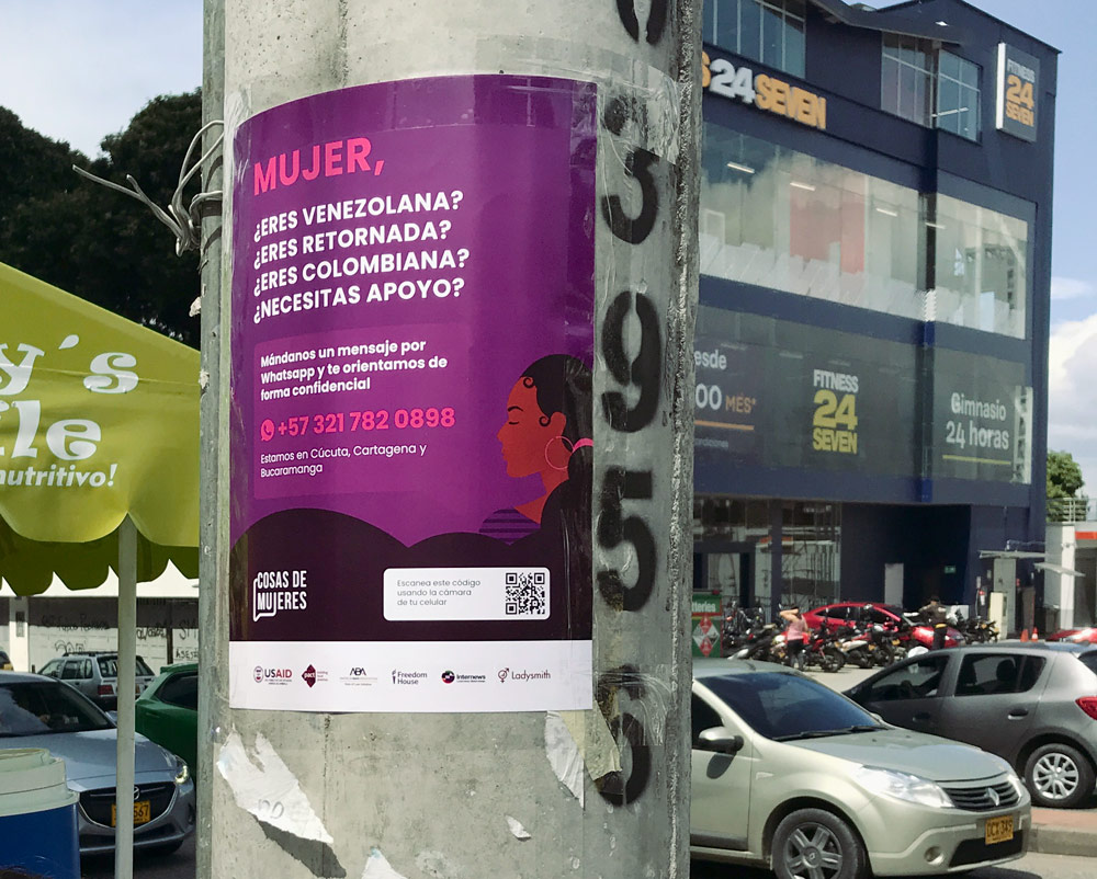 Awareness poster on street pole -  An invitation to message the Cosas de Mujeres Helpdesk on WhatsApp.