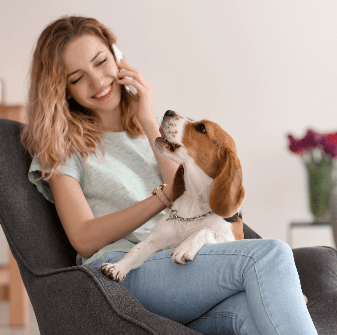 Smiling young blond woman strokes her dog.