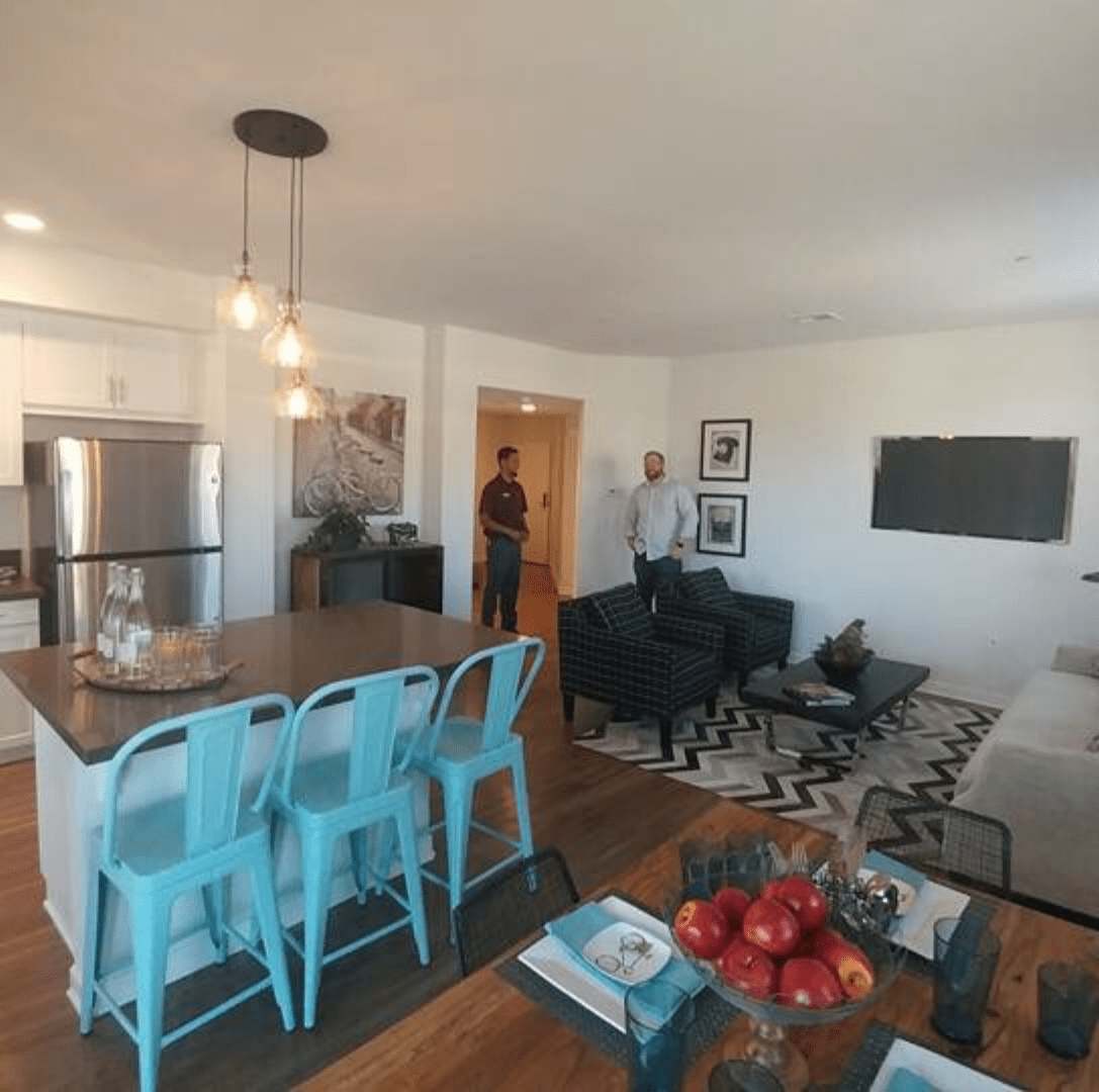 Wide-lens view of a well-decorated kitchen living room.
