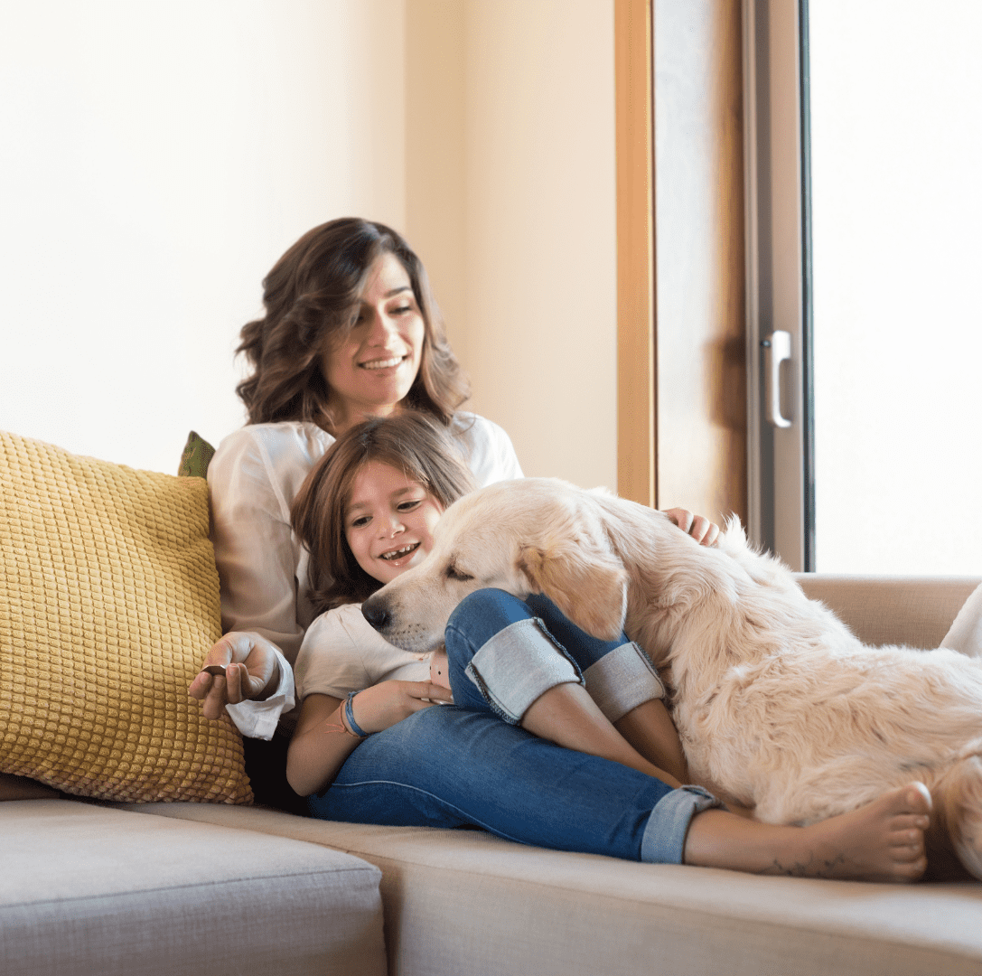 A brown-haired woman reclines on a sofa with a small child.