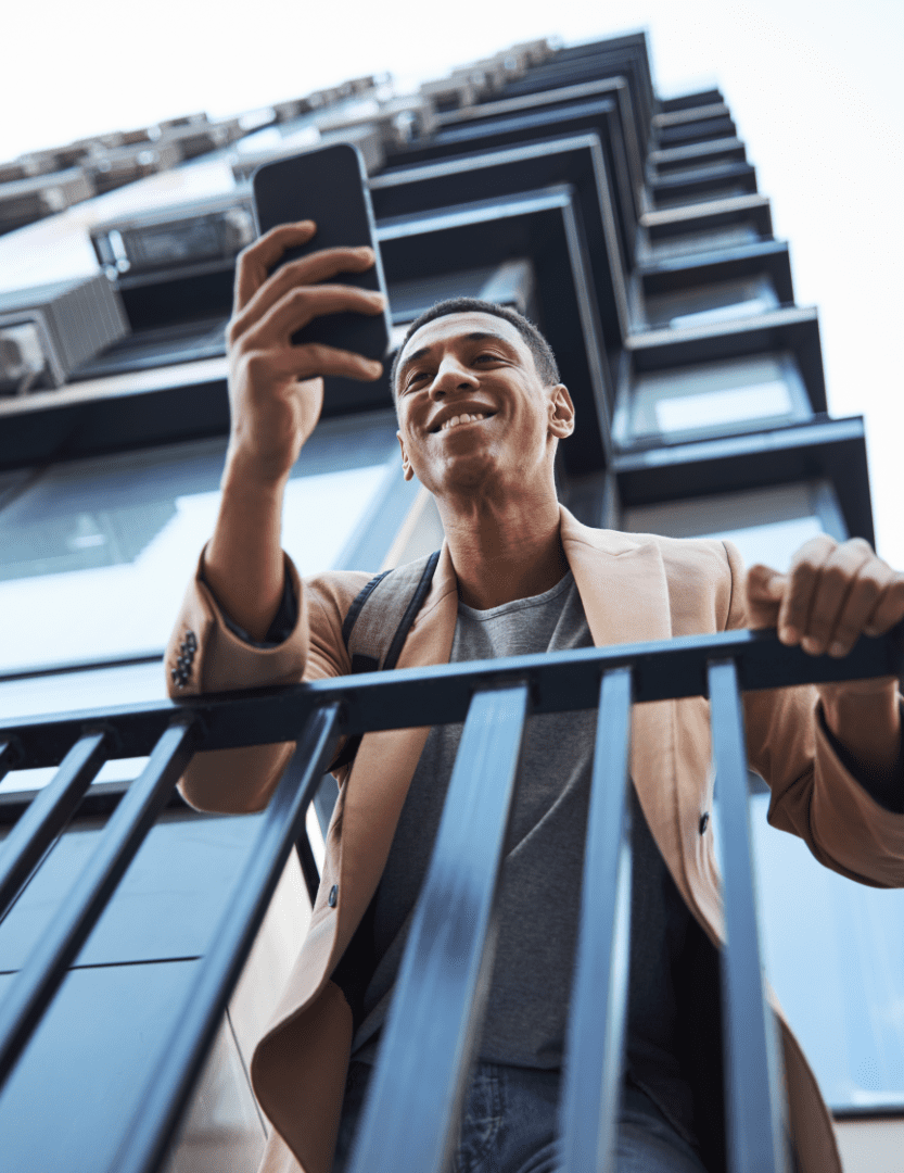 View from below of a man leaning over a balcony and checking his phone.