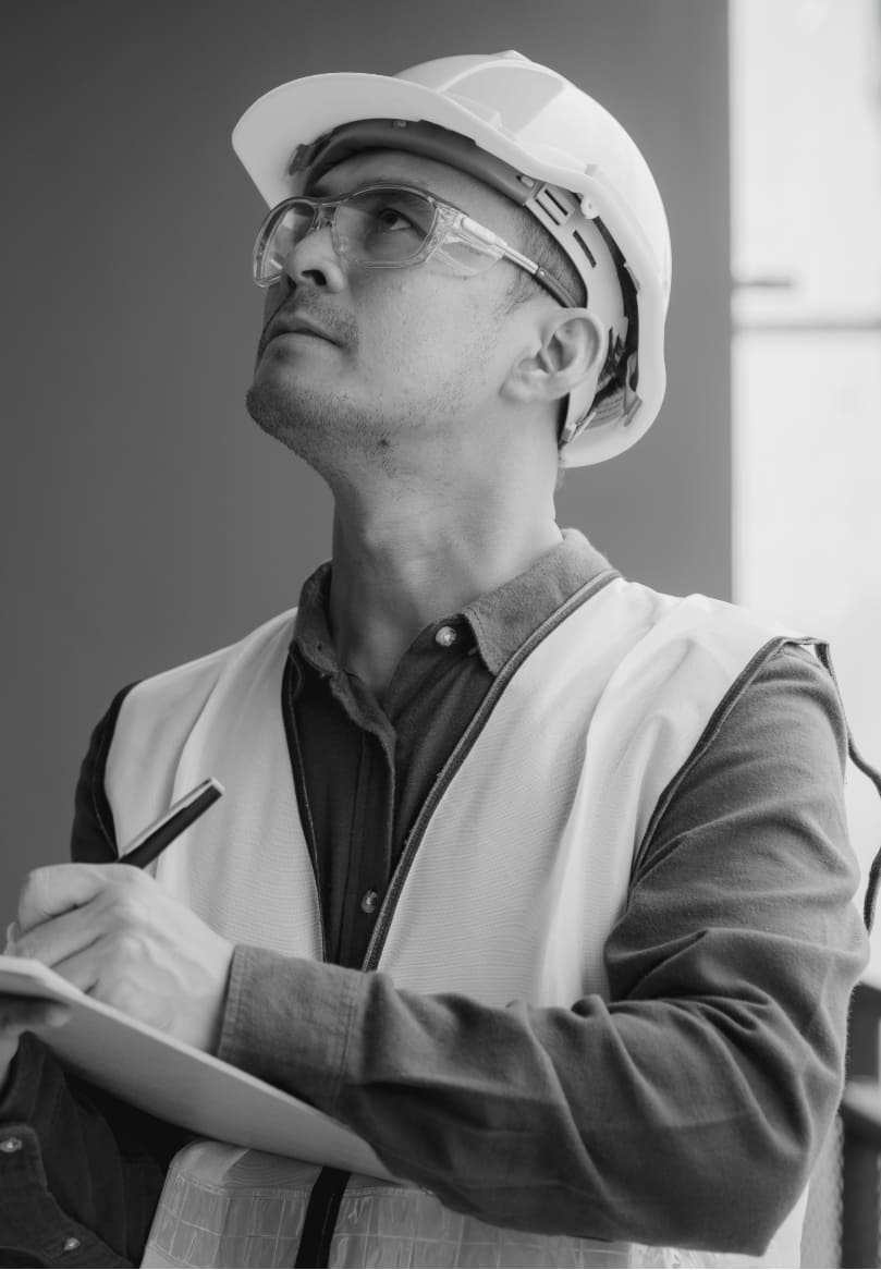 Black and white image of a contractor wearing a builder's hat.