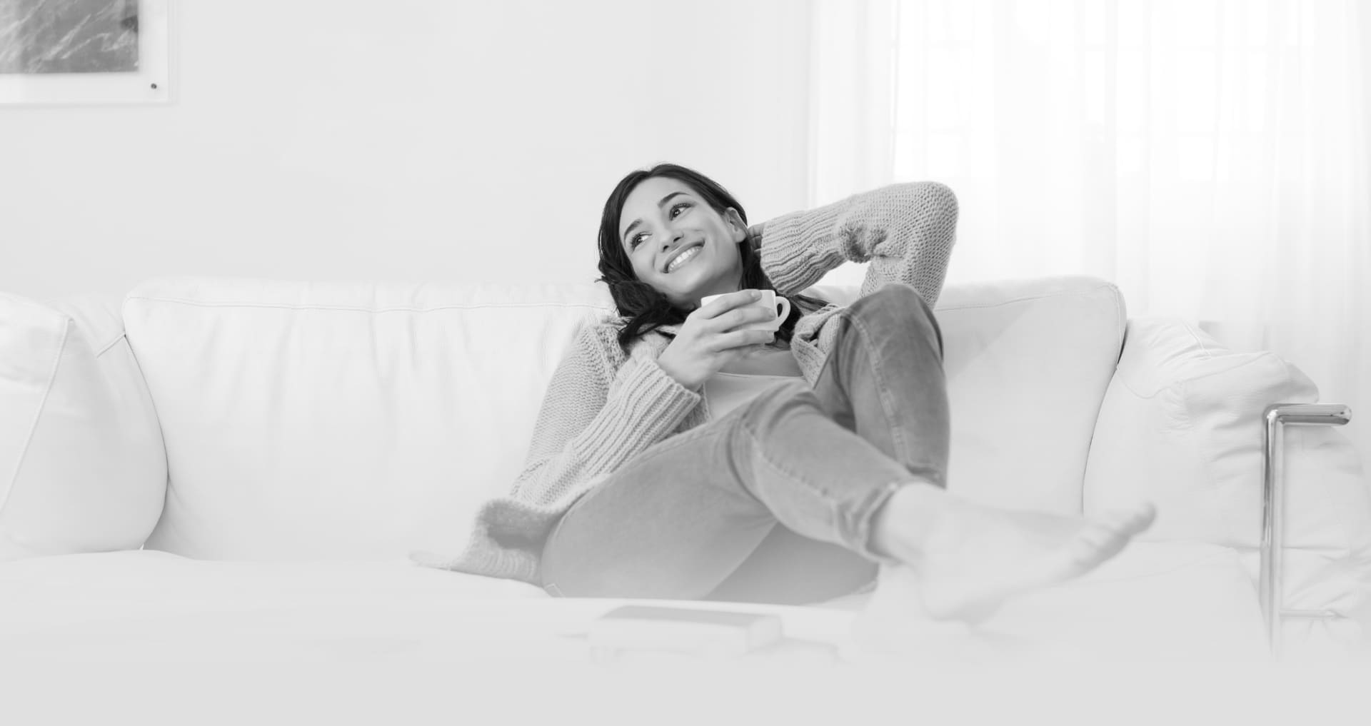 A young woman reclines on a sofa, smiling and relaxed.