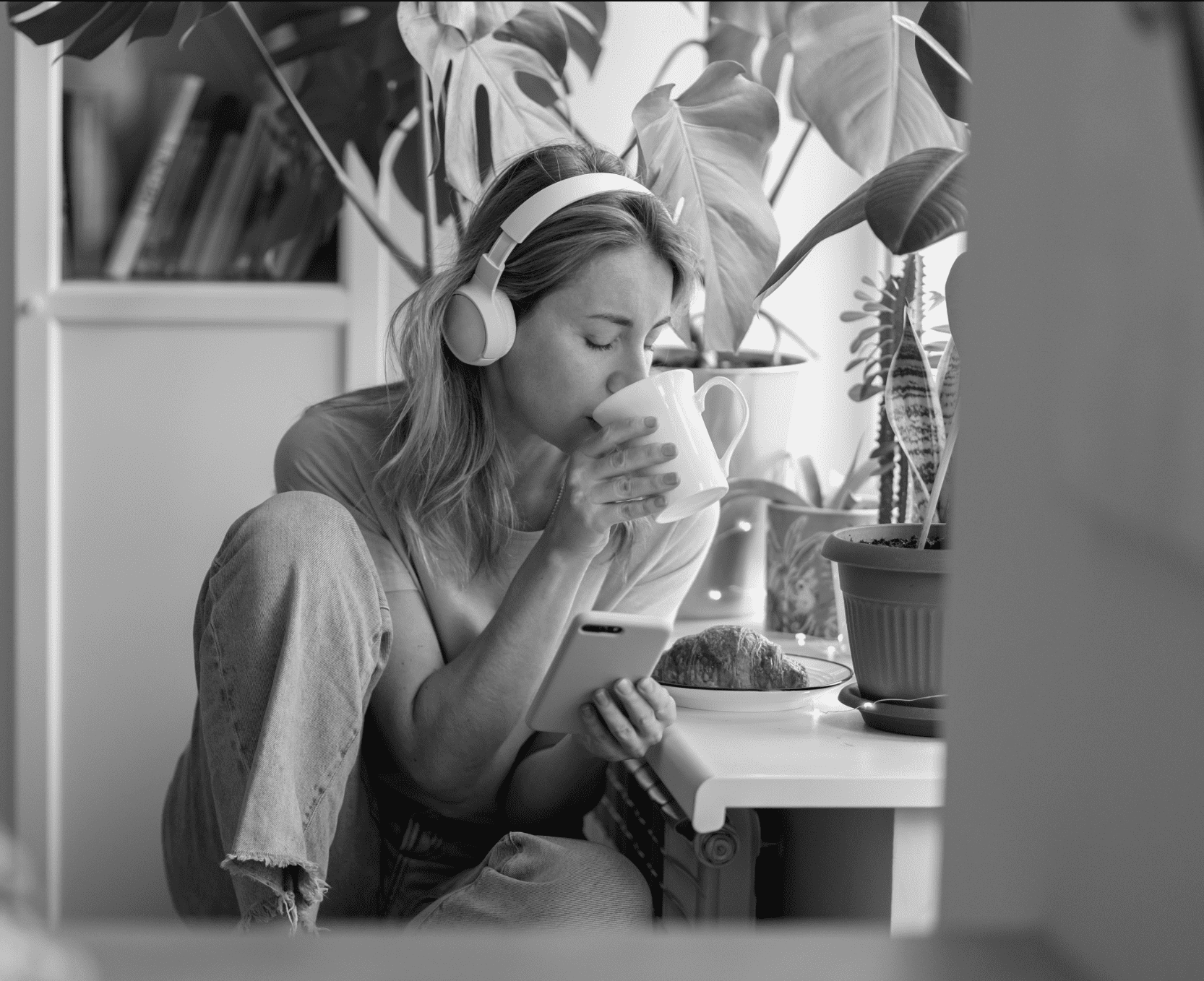 A woman wearing headphones sips from a mug.