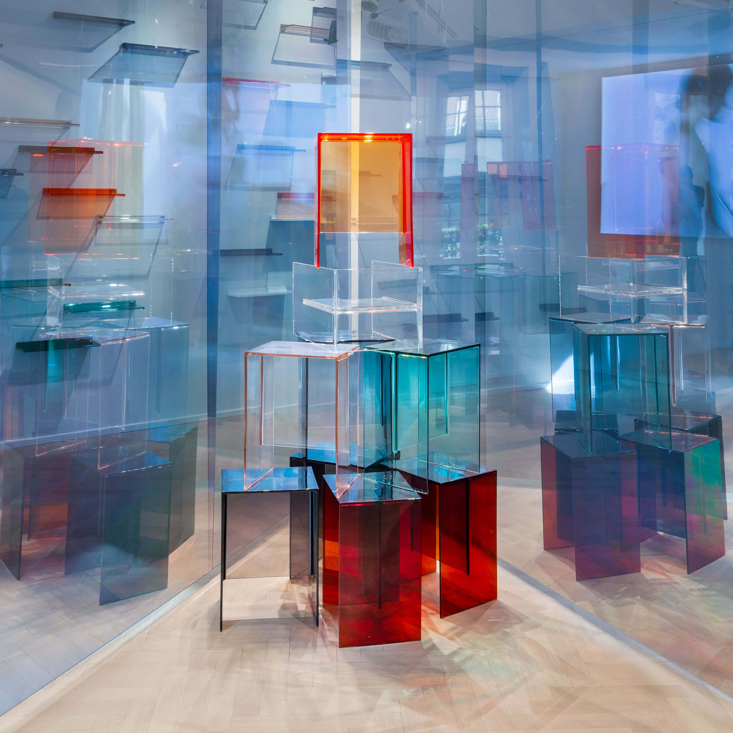 Colored semi-transparent furnitures arranged to sculptures surrounded by transparent walls and mirrors.