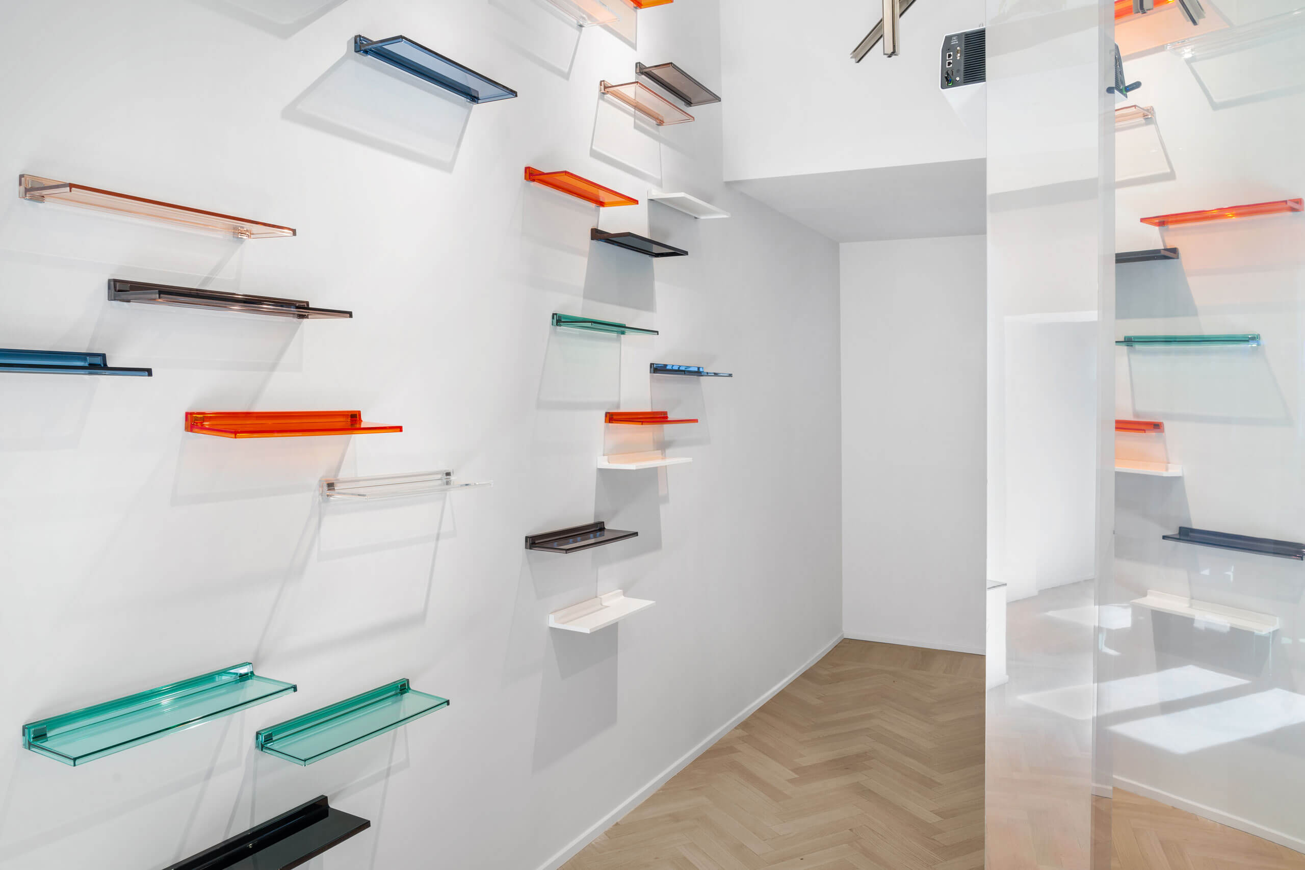Colored semi-transparent shelves arranged on the wall of the main exhibition room of Laufen space Milano.