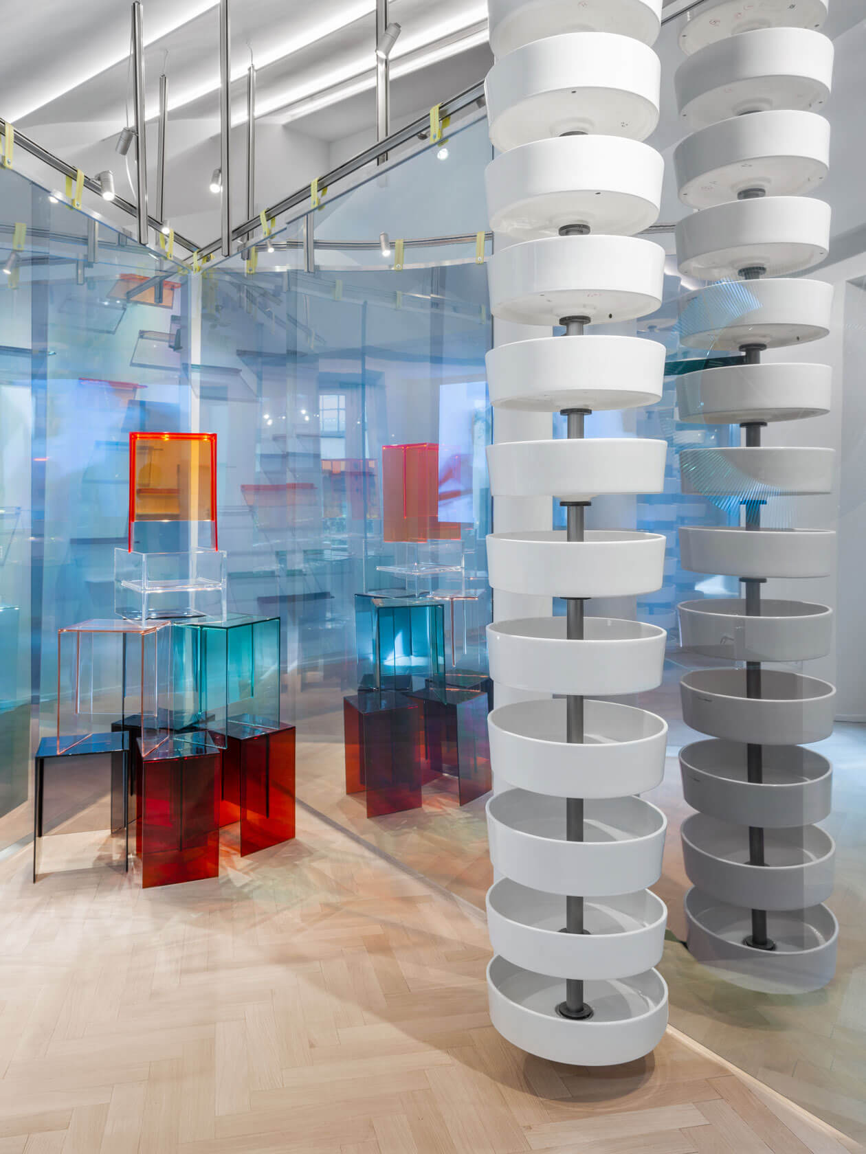 Washbasins and colored semi-transparent furnitures arranged to sculptures.