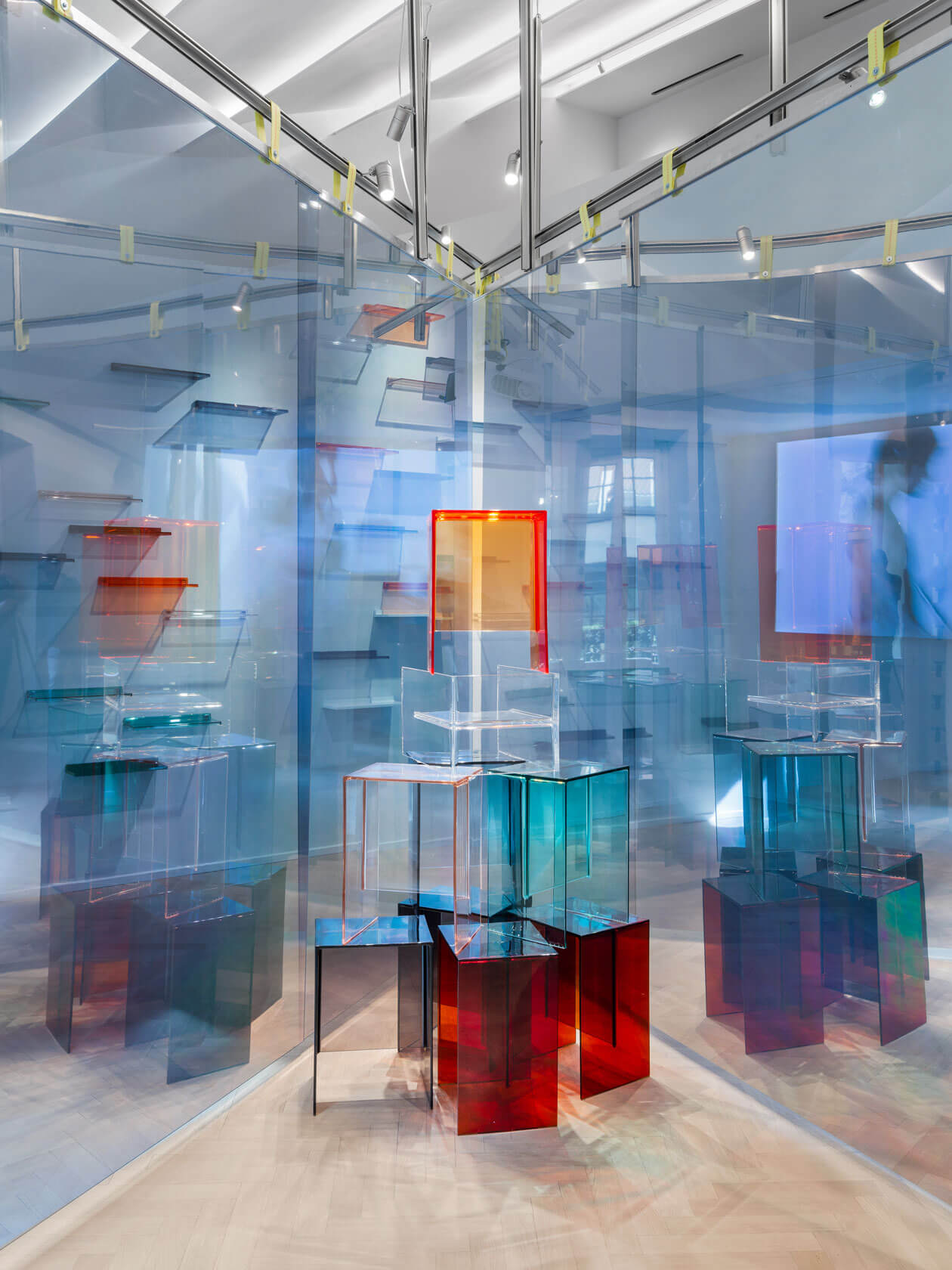 Semi-transparent colored stools which are arranged as a sculpture behind blueish  walls.