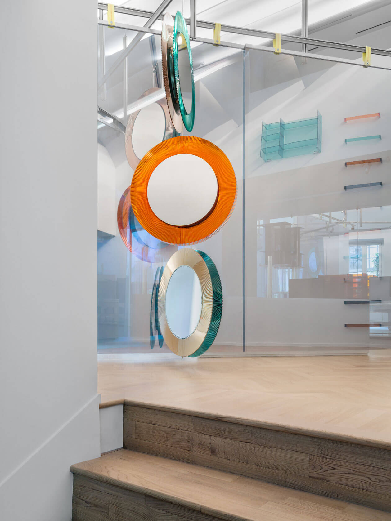 Round mirrors hanging like a mobile from the ceiling reflected in a mirror wall.