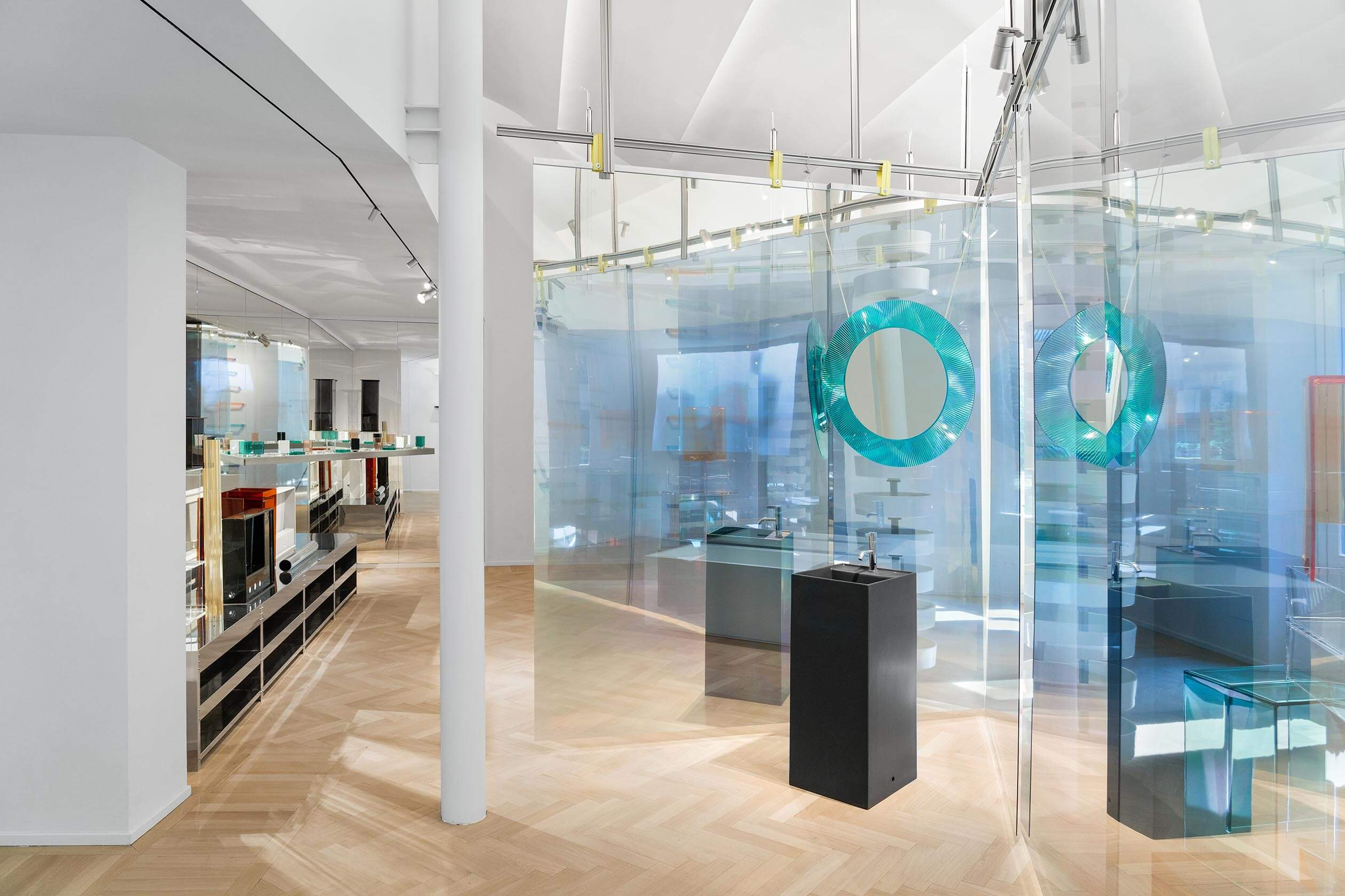 Part of the exhibition with glass walls, mirrors and standing black Kartell by Laufen washbassins.