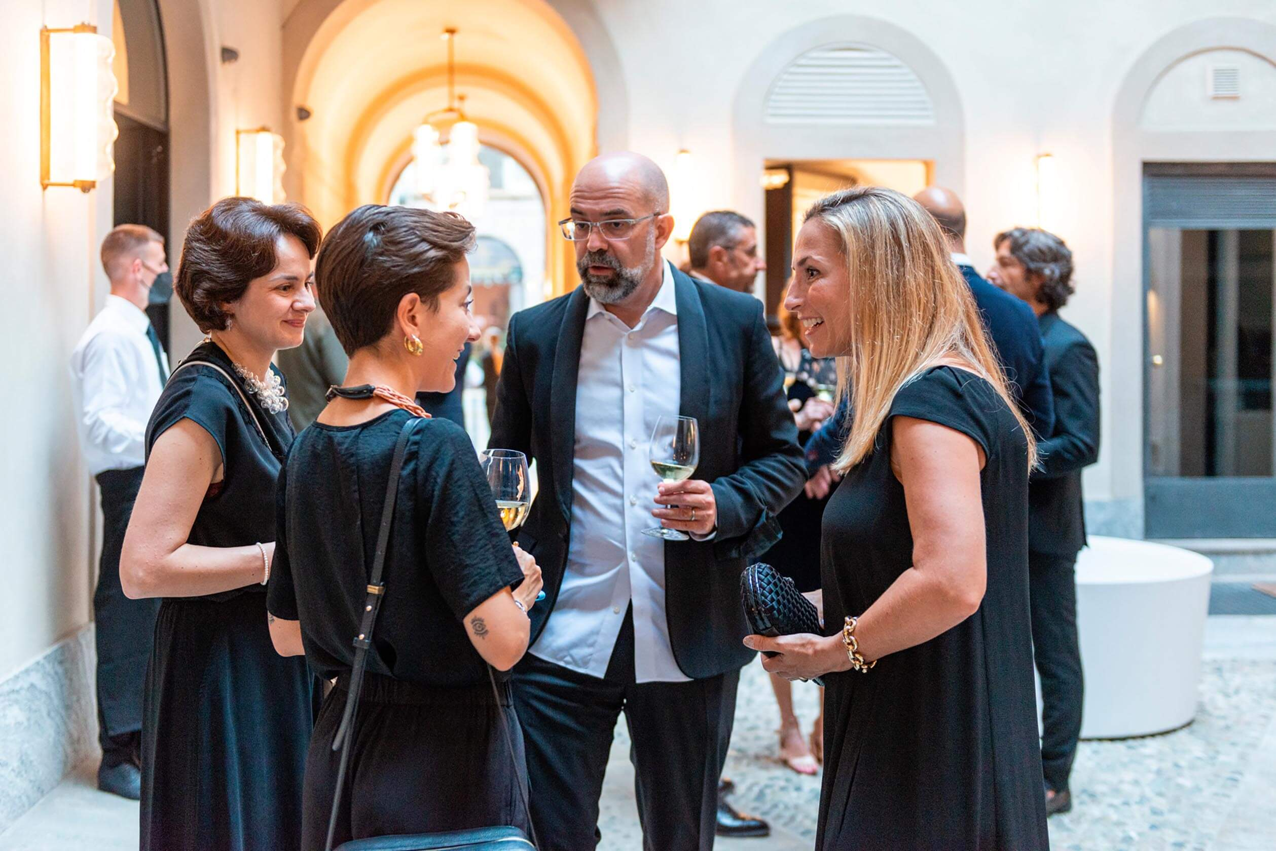 Antonio Linares talking in a group in the square of Laufen space Milano during the festive dinner event.