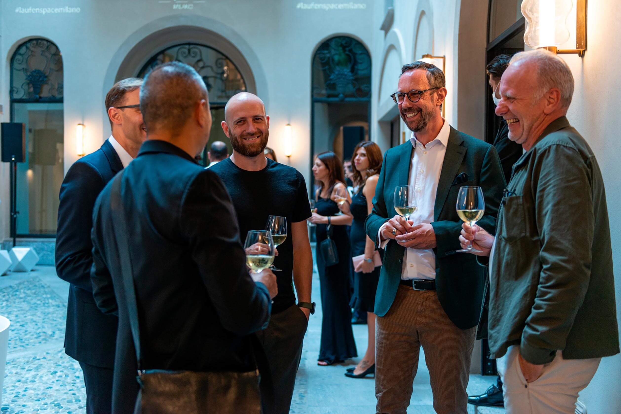 Roger Furrer among other chatting in square during Laufen space Milano event.