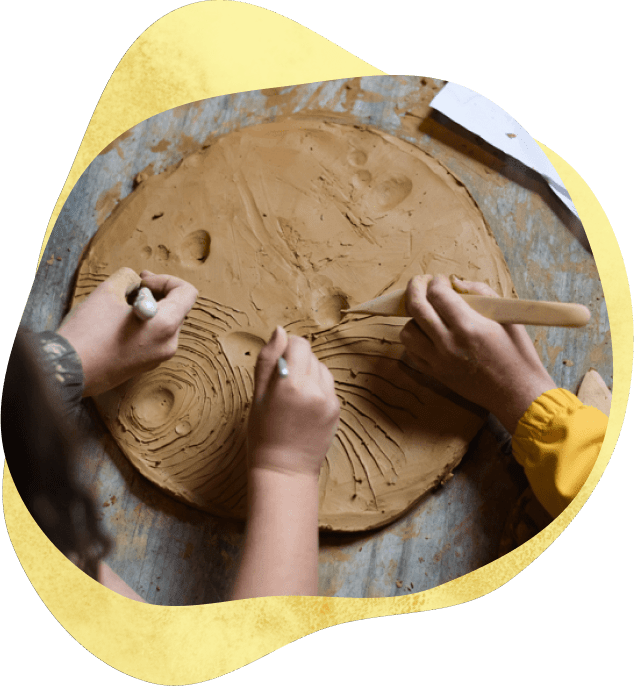 Children's hands using tools to carve patterns into clay.