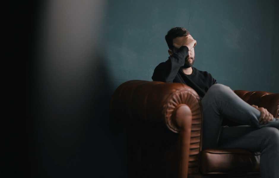 Trist mann som sitter i en stol