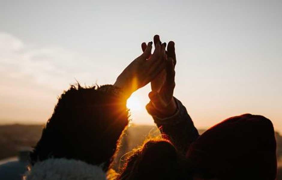 Par holder hendene opp mot solen