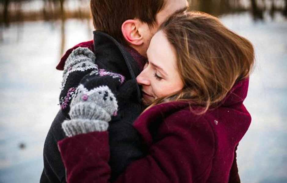 Kvinne som klemte mannen sin en vinterdag