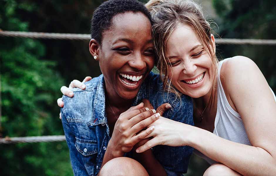 To kvinner sitter tett sammen og ler   Parweb - Parterapi på nett