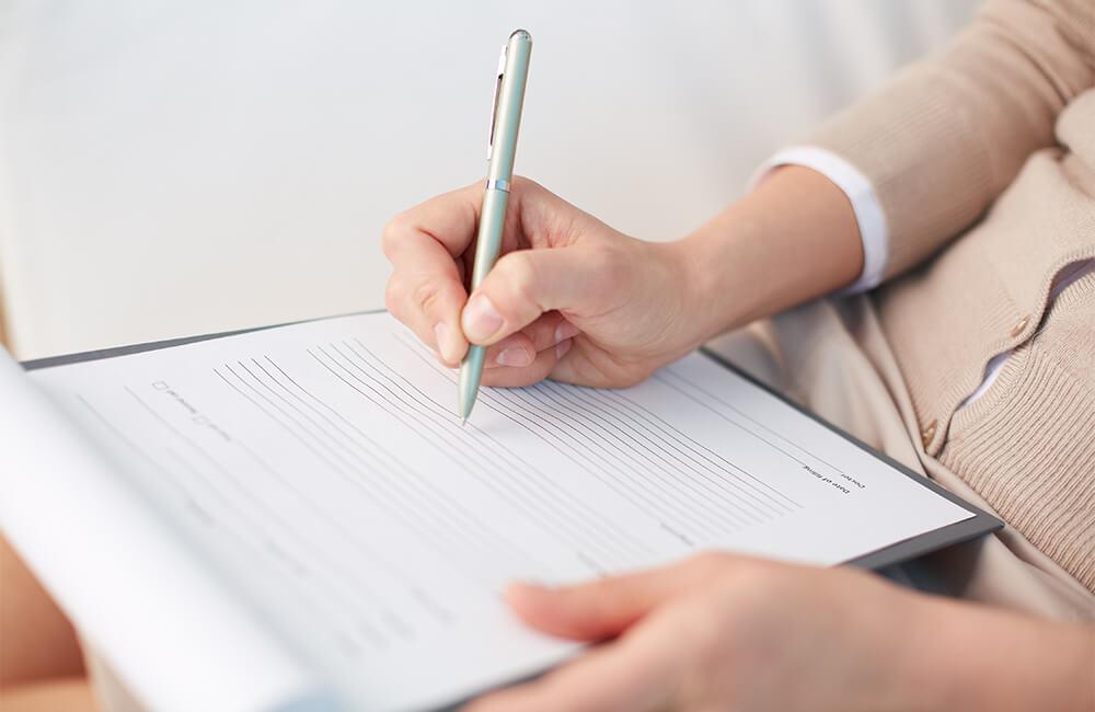 A patient filling out a new patient form.