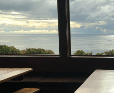 A photograph of a room containing wooden tables and padded benches. A large window looks out over the ocean.