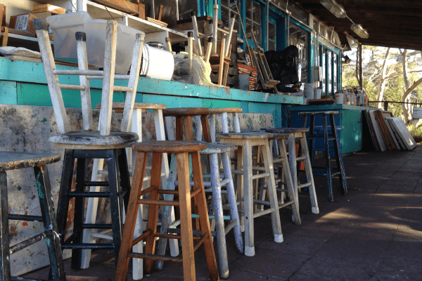A photograph of wooden stools in lined up along a blue countertop.