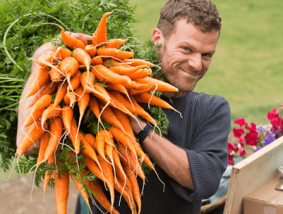 A photograph of a smiling man with light skin, brown hair, and a gray shirt, holding a large bunch of carrots on his shoulder.