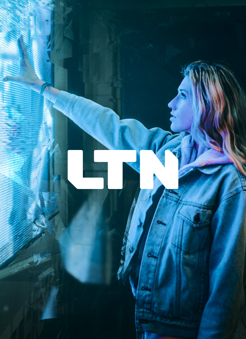 Woman in jean jacket touching large, interactive screen wall. Overlay of LTN logo on photo