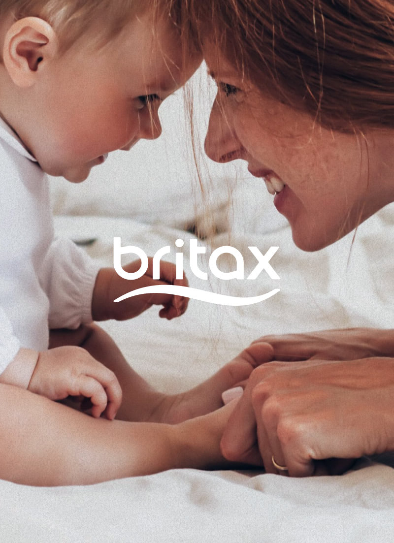 Mother and baby smiling, touching heads on bedsheets. Britax logo overlays the photo