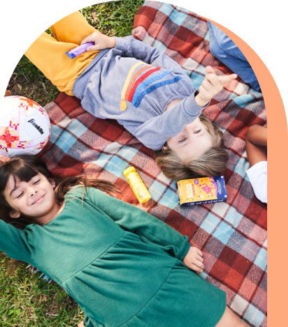 Kids laying on a blanket with a box of Bitsy's Swish and a soccer ball.