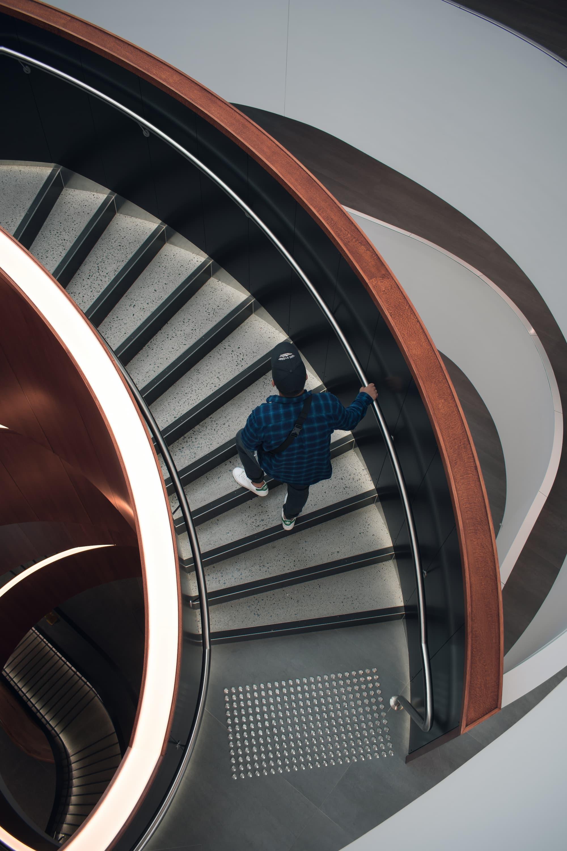 Man walking up spiral staircase