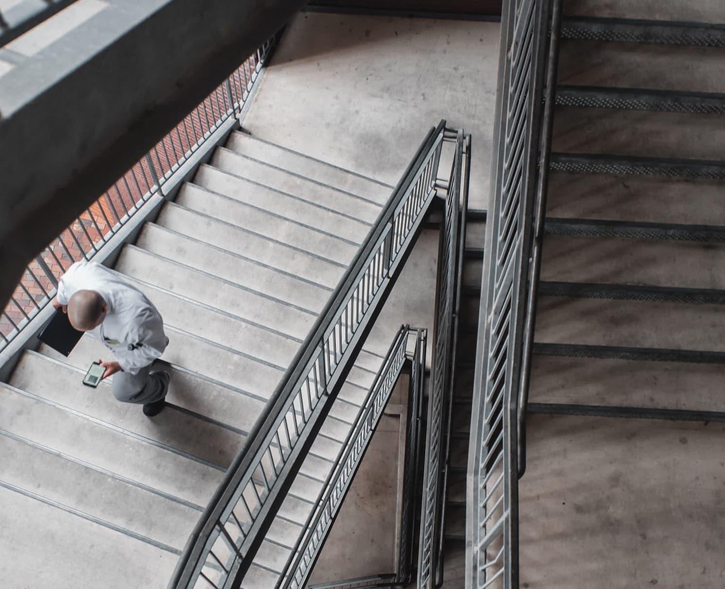 Man on phone walking up stairs