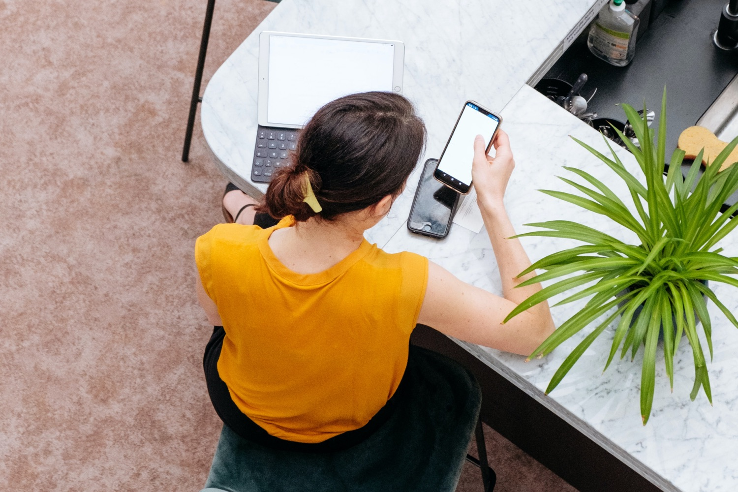 Woman at a table with laptop and phone in hand.