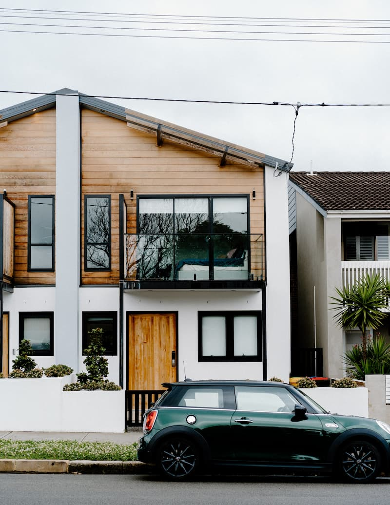 A two storey house, with a green car parked out front