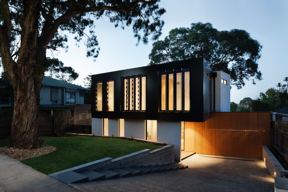 A new modern house at dusk with lights on inside.