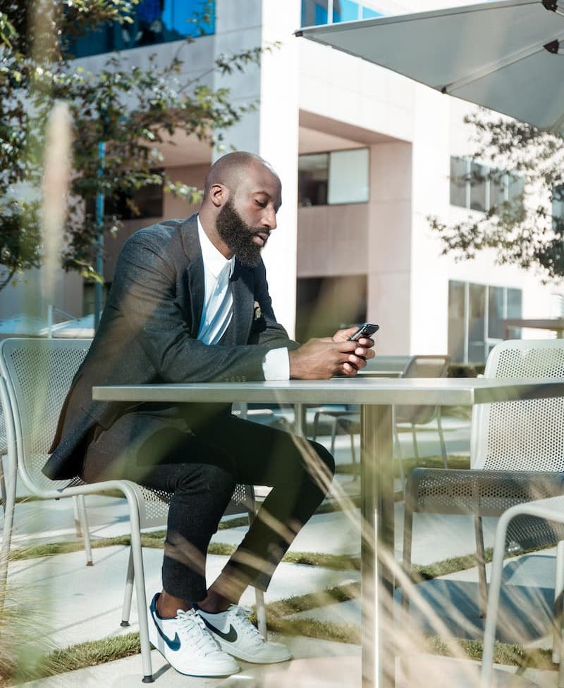 An image of a man at an outdoor table, looking at his phone.