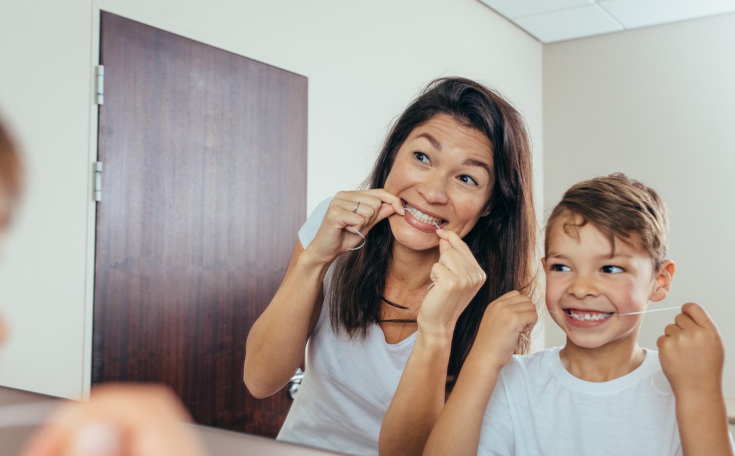 Bilde av mor og barn som bruker tanntråd