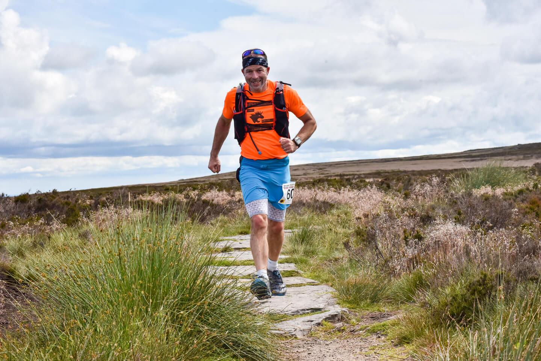 Man running across a moorland path in ultramarathon race.