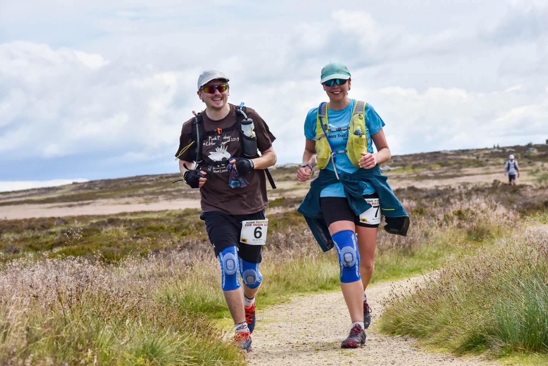 Man and woman running across moorland in ultramarathon race.