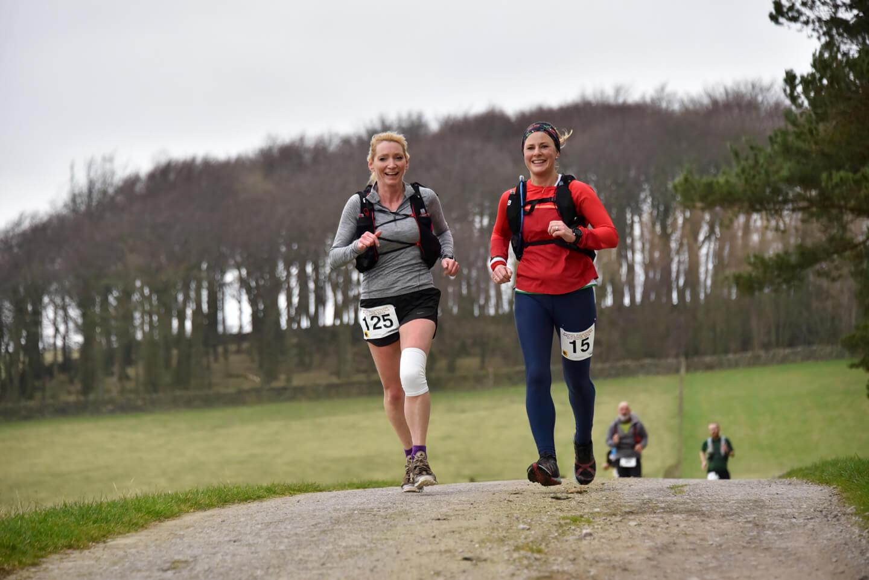 two women running through parkland in ultramarathon race.