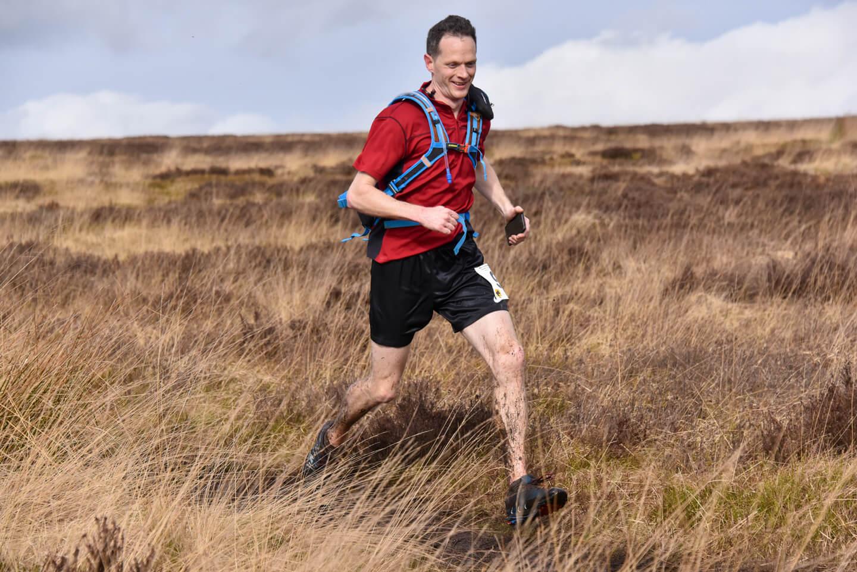 Man running across muddy moorland terrain in ultra marathon race.