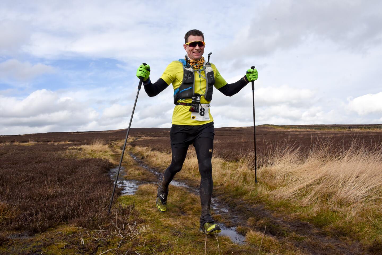 Man using walking poles across a muddy moorland track in ultra marathon race.