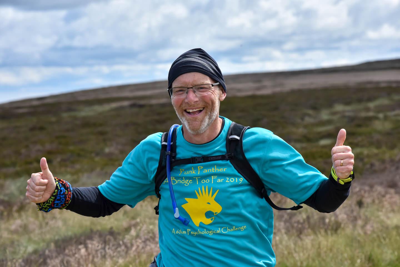 An ultramarathon competitor gives two thumbs up during an ultramarathon event over moorland.